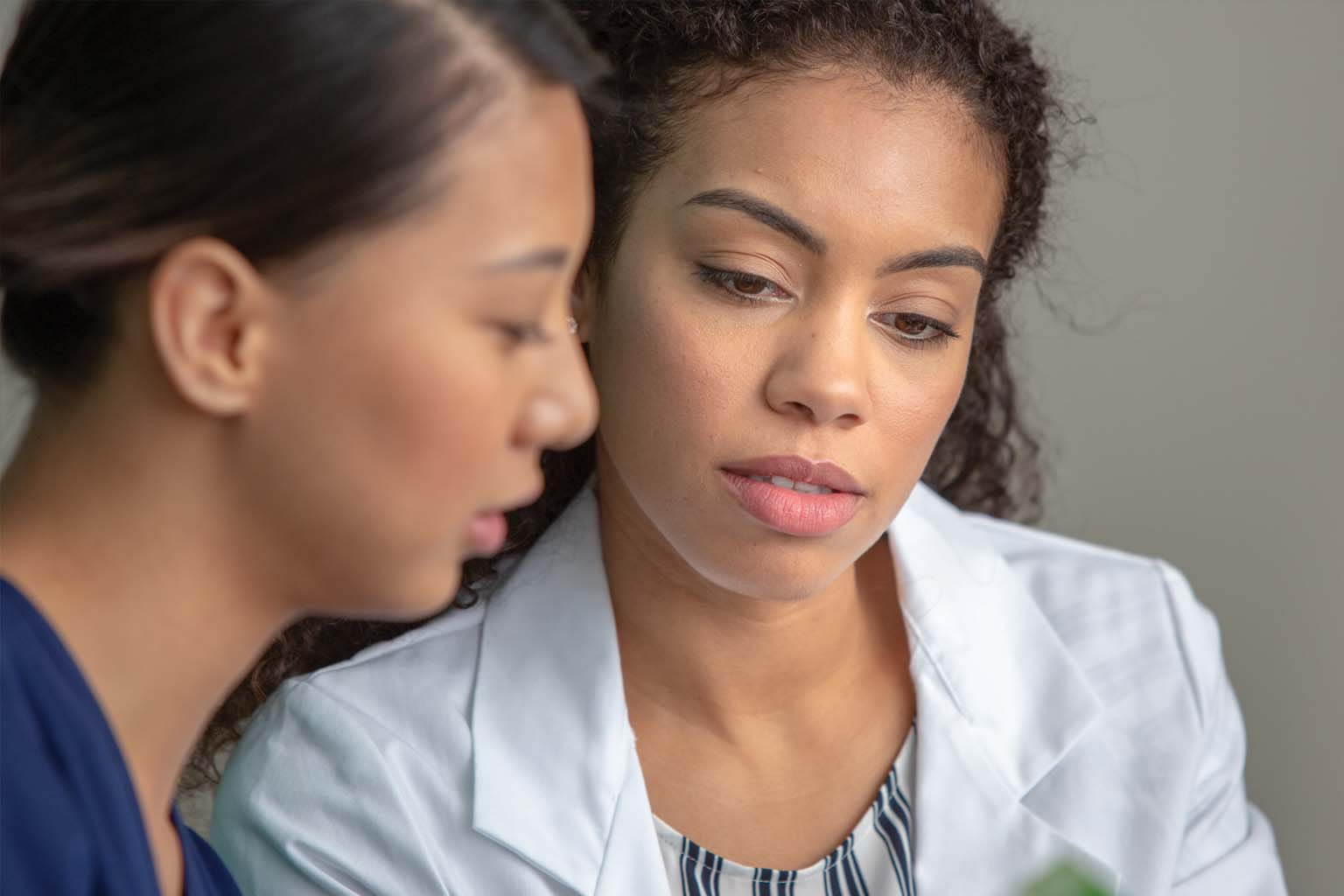 closeup of nurse and doctor talking, referring to data