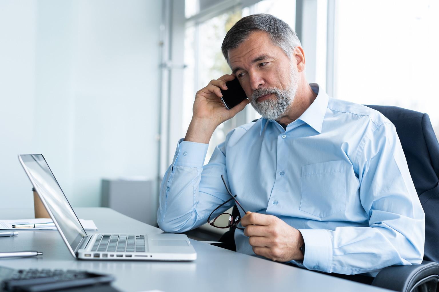 Manager w szpitalu rozmawia przez telefon i patrzy na laptop z otwartym programem Progmedica