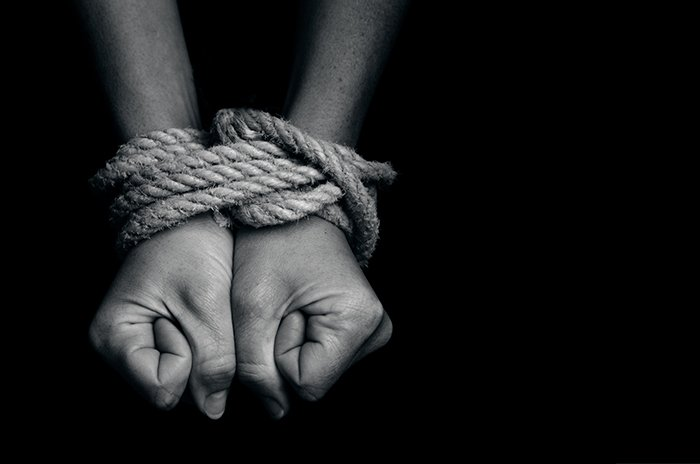Hands tied together with thick rope