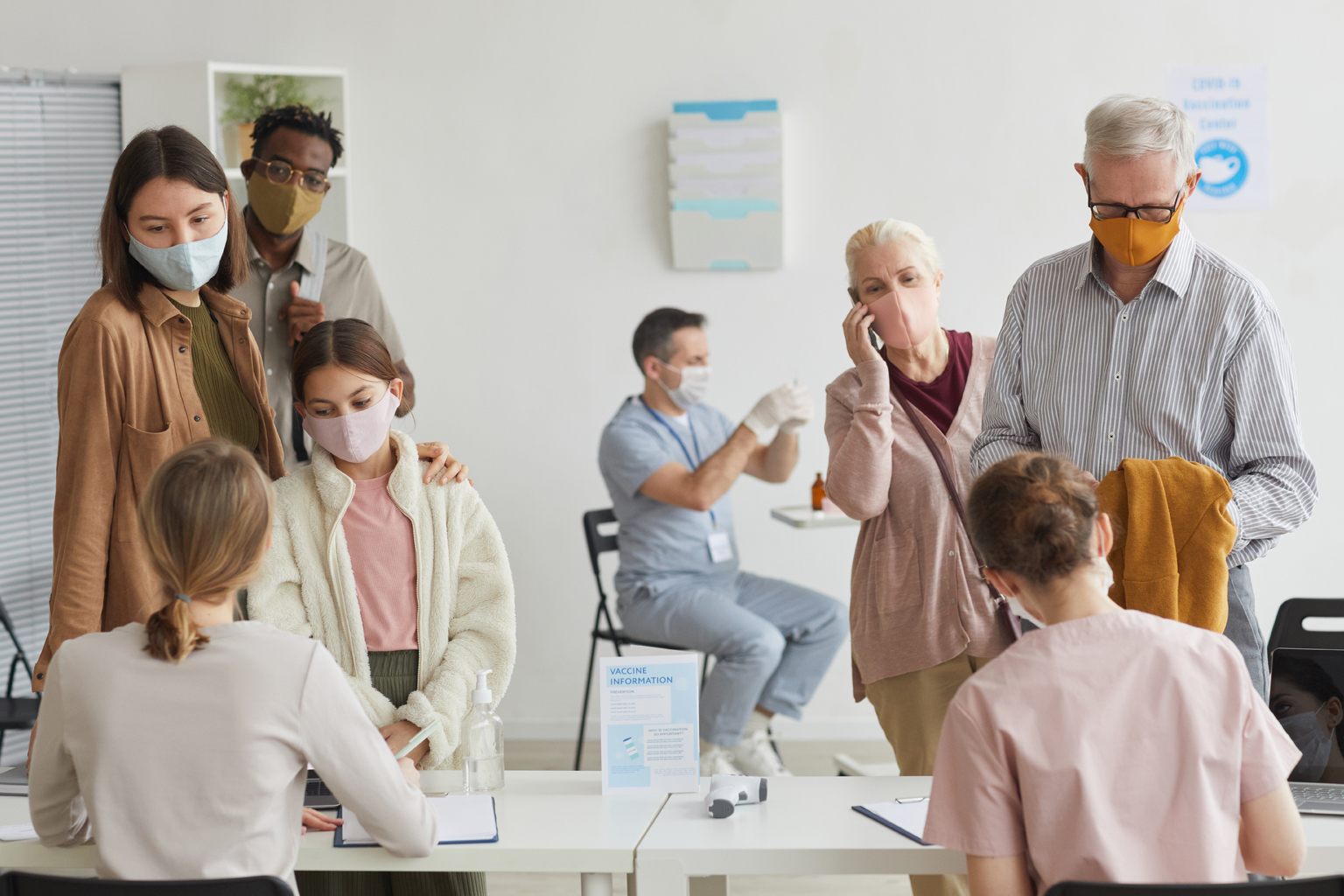 Group of patient wearing face masks, standing in lines at vaccine check in desk