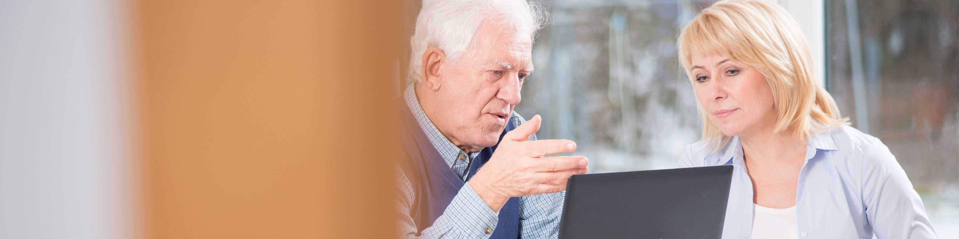 Man and woman looking at laptop and discussing