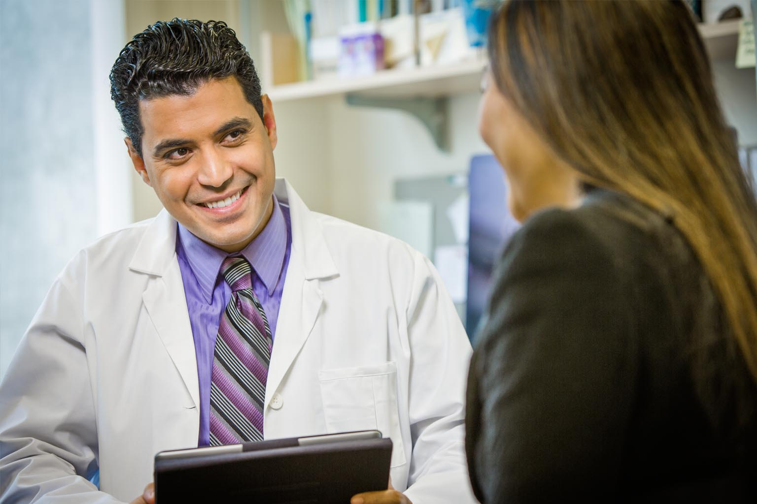 male doctor with tablet talking to female patient