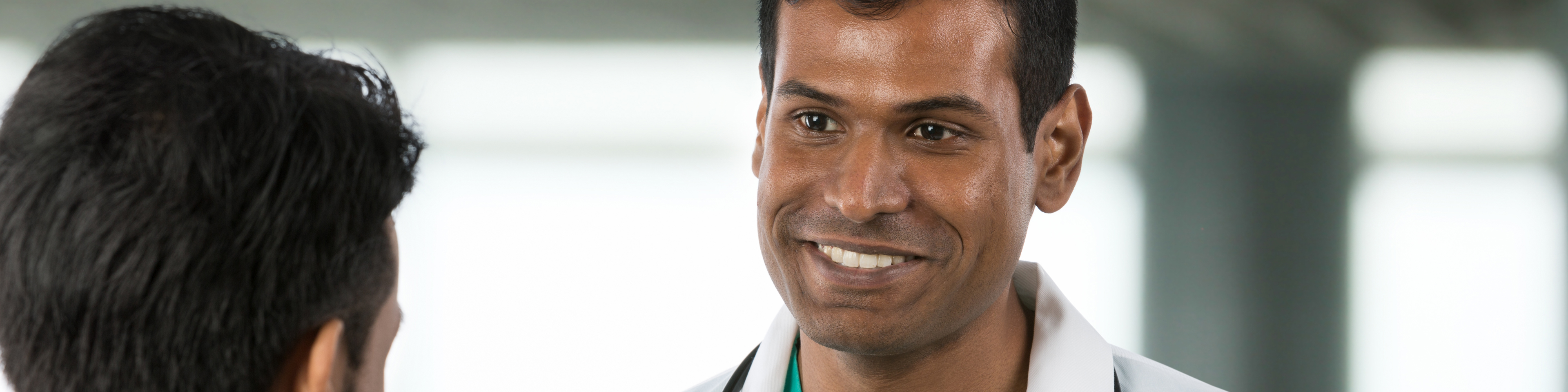 Doctor standing with and smiling at patient in open hospital area