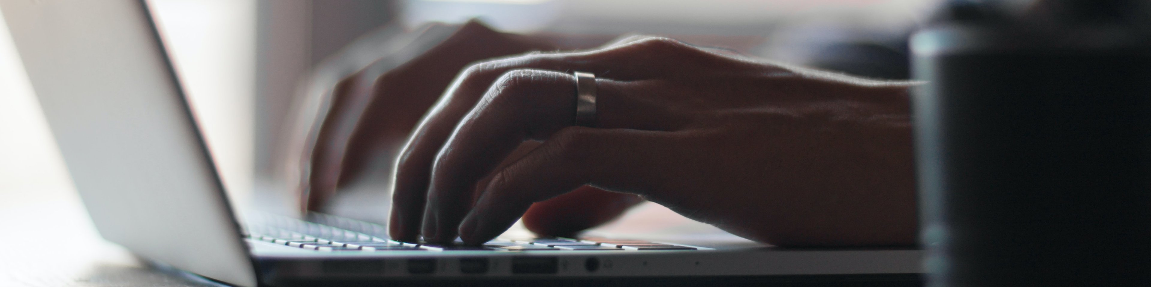 Close up on hands working on a laptop at a table
