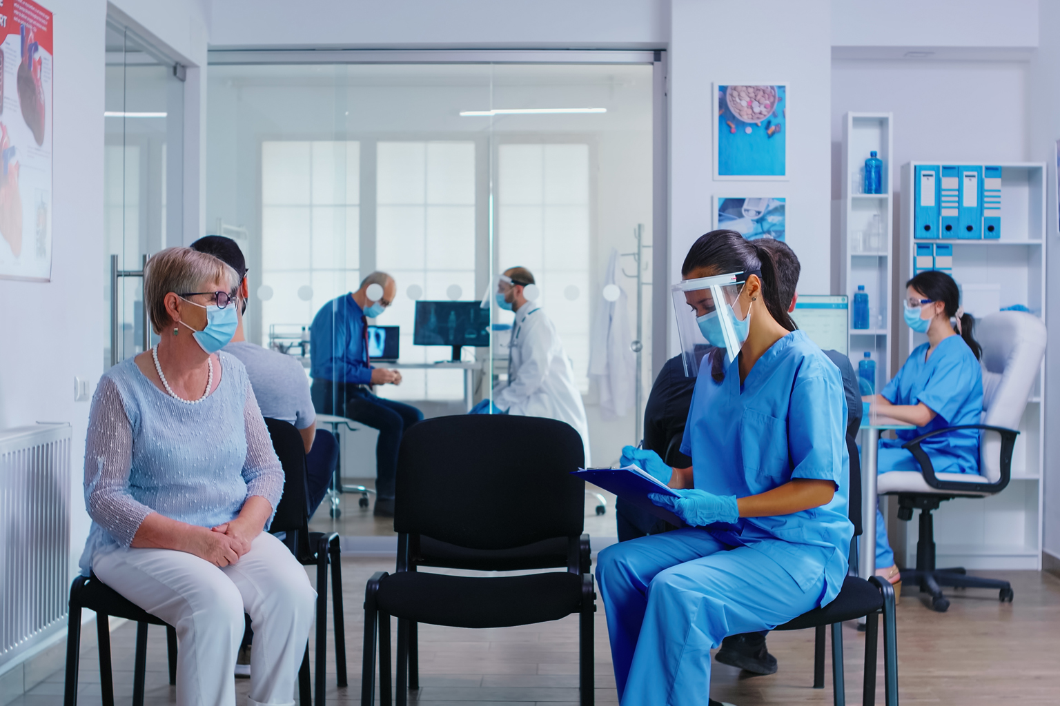 Busy healthcare office with socially distanced workers and patients