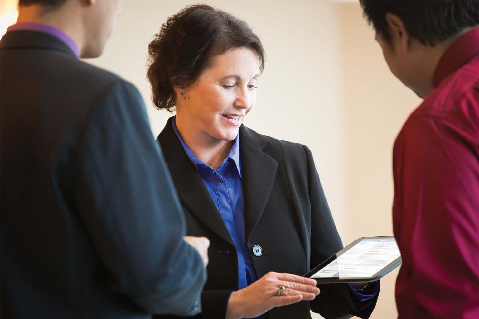 executives viewing tablet and talking