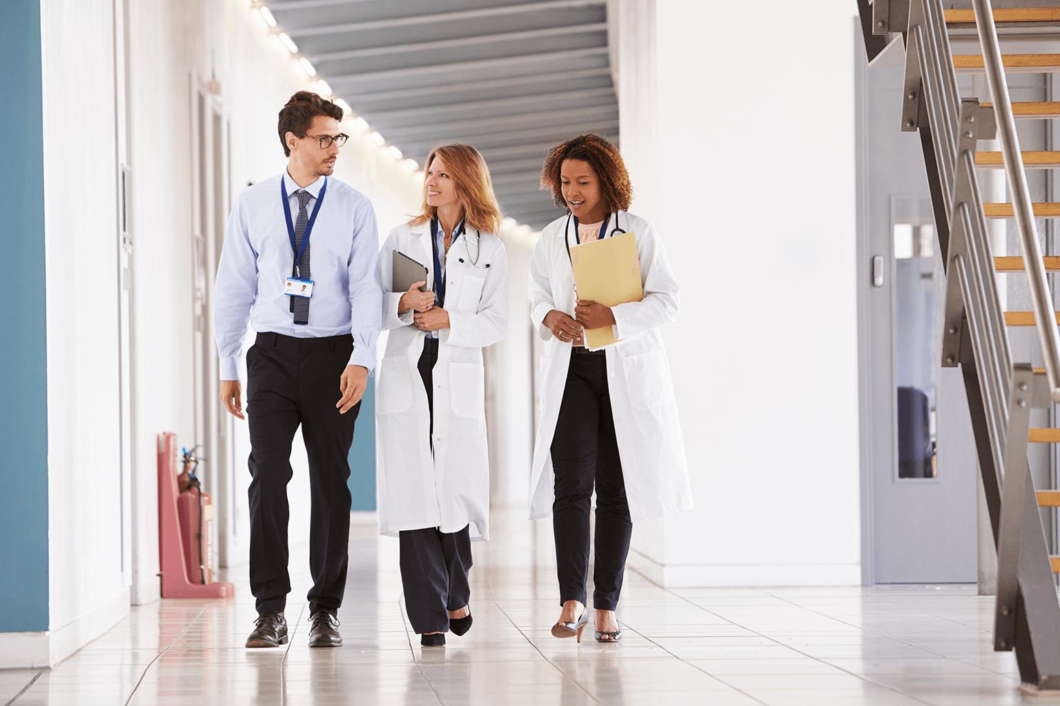 clinicians-walking-down-hallway-in-hospital
