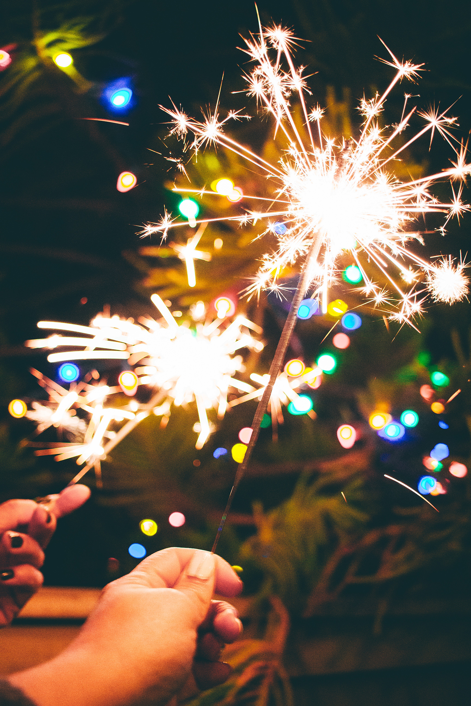 Close-up on two different people's hands holding sparklers