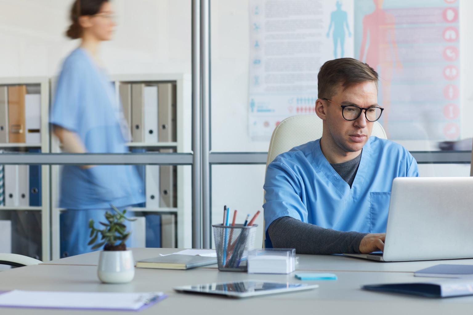 Lekarz pracuje na komputerze w programie Progmedica, w tle widać pielegniarkę