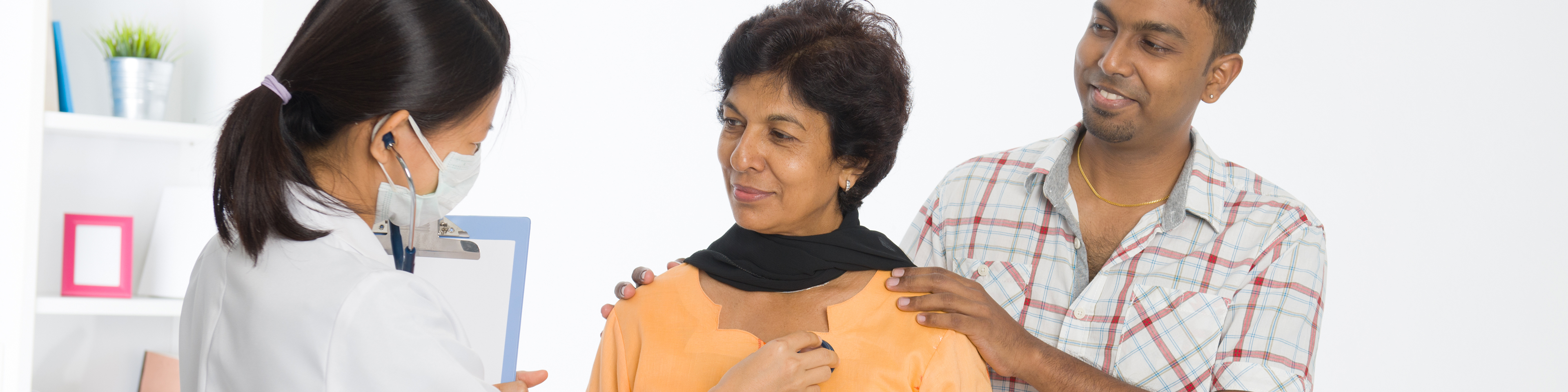 Doctor checking patient's upper chest with stethoscope while supportive family member is standing next to patient