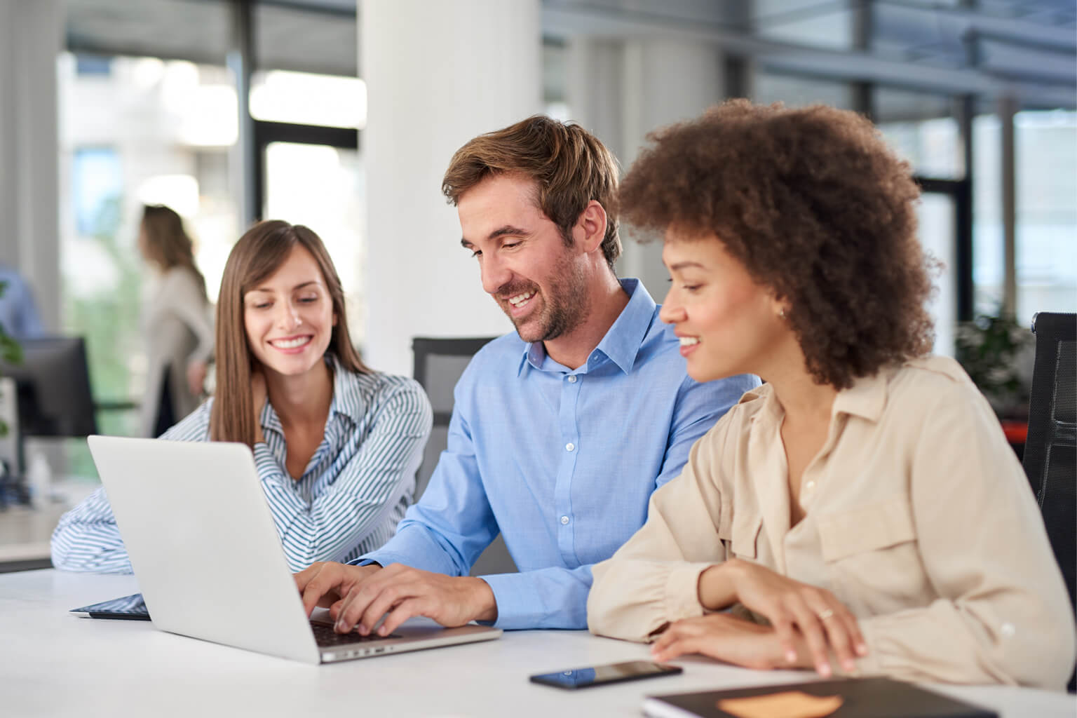 Three people surrounding a laptop