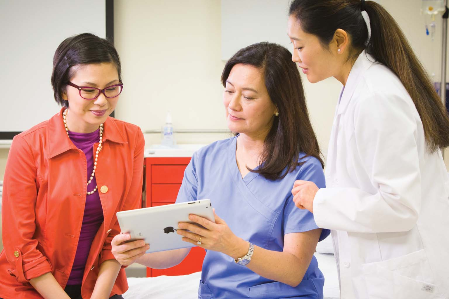 doctor with patient viewing tablet