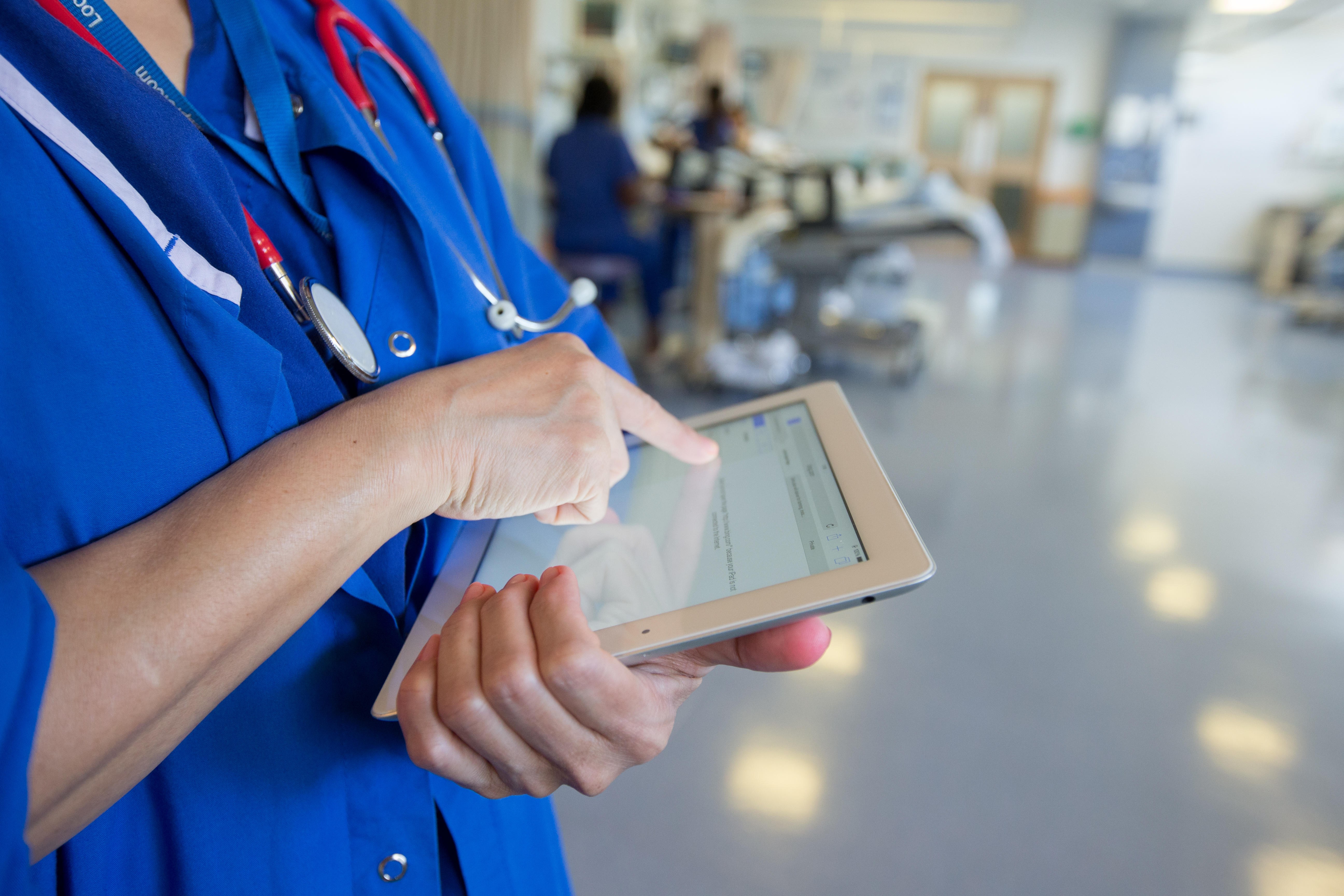 Closeup of a medical professional working on a tablet