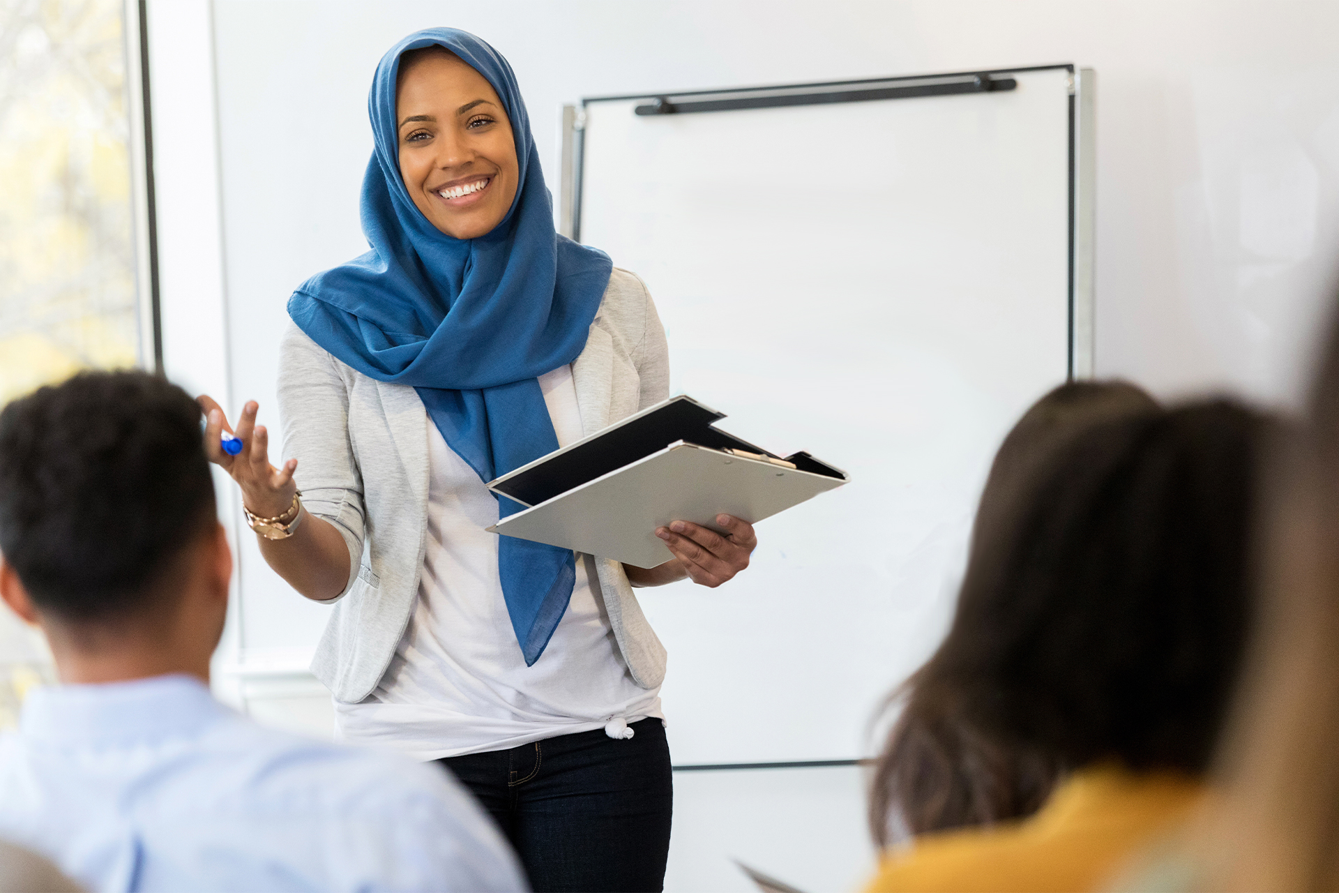Educator standing in front of sitting group of students