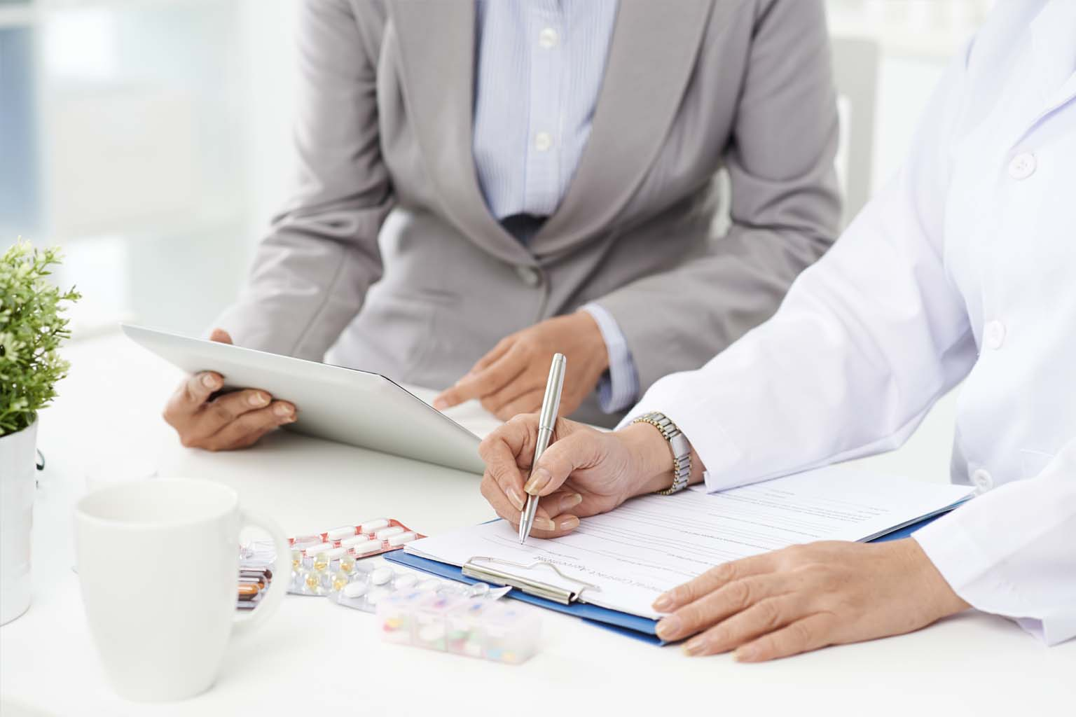 business meeting with medication sample, tablet, and contract