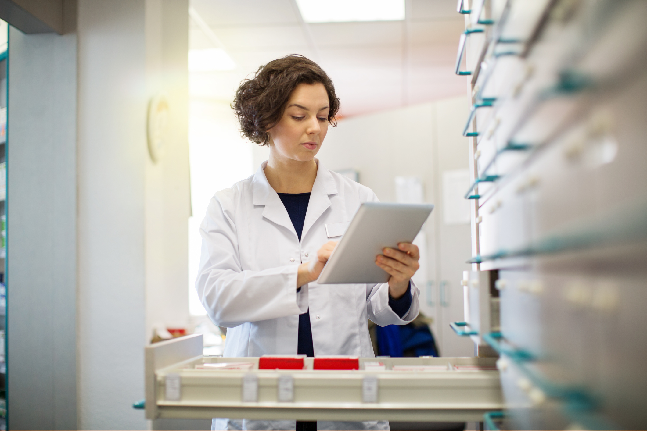 pharmacist completing compliance check list on her ipad