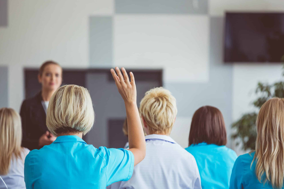 Healthcare professionals in a classroom, woman with hand raised