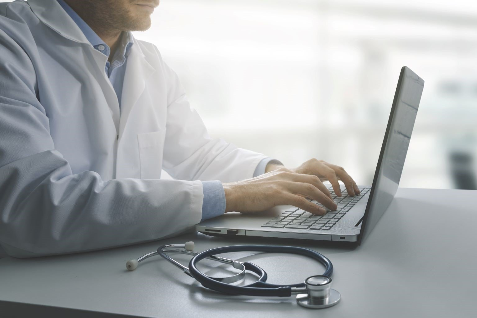 Male doctor typing on laptop at desk.