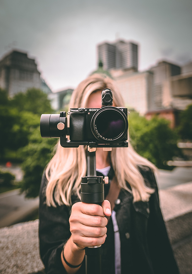 Woman holding a monopod with camera in front of herself, hiding her face