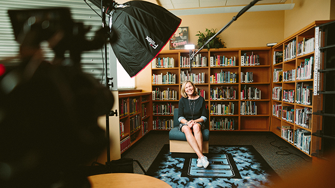 Woman sitting in a library for an interview, image taken from behind equipment including camera