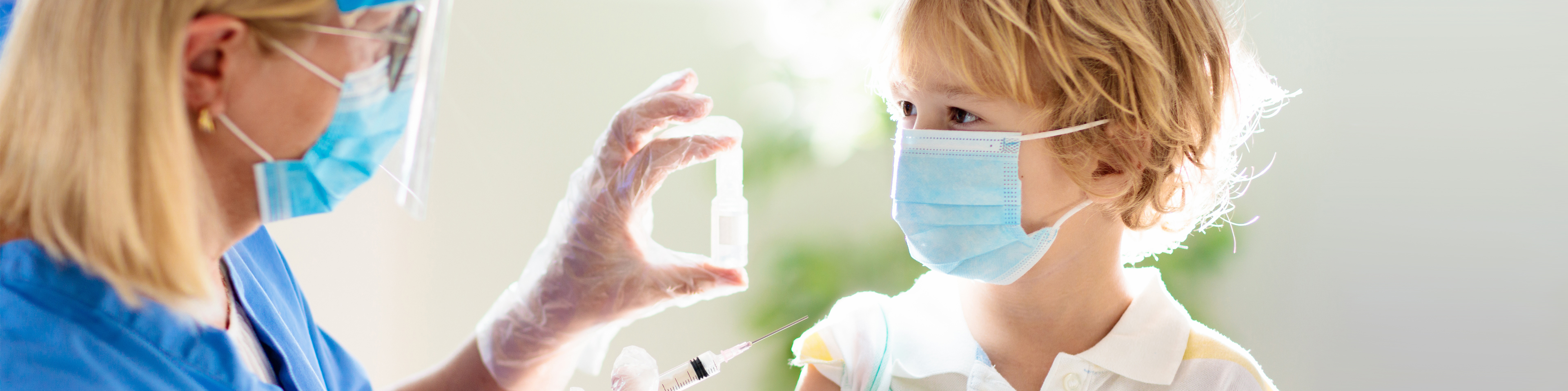Mask and face shield wearing nurse getting ready to give mask wearing child a vaccination shot