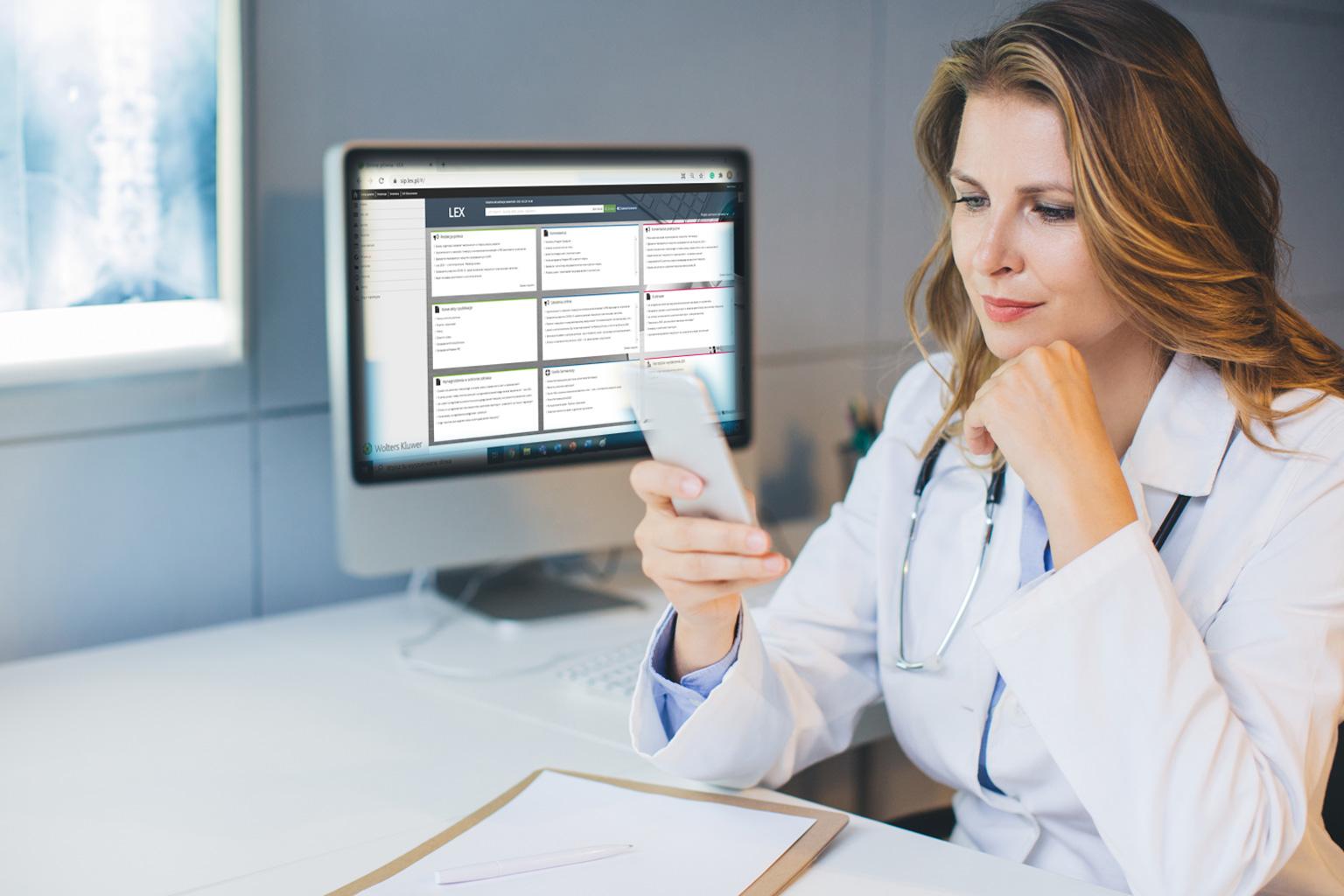 Lekarka patrzy na telefon, za nią jest komputer z LEX Compliance Medica