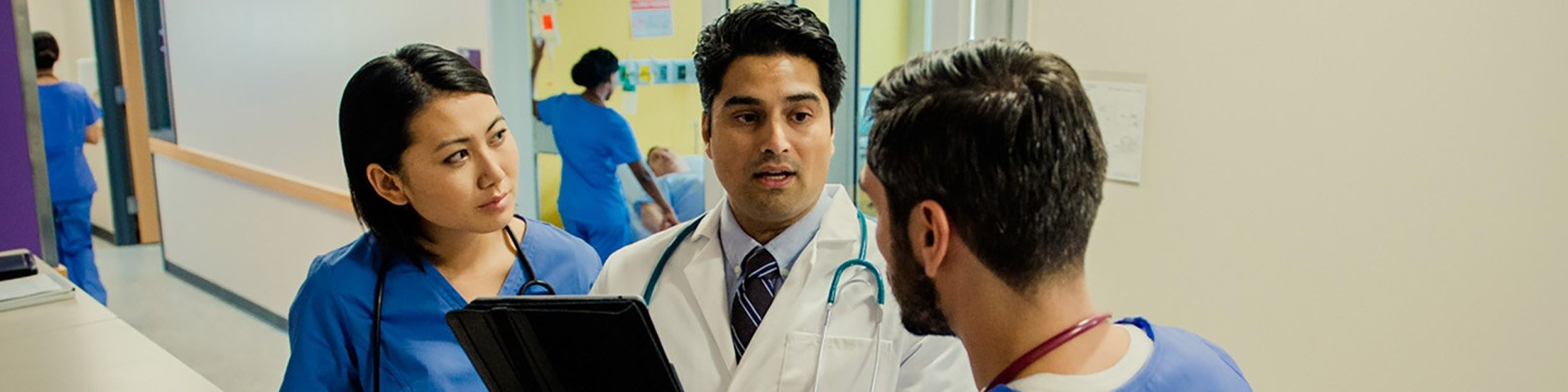 Doctor speaking with male and female nurses at nursing station