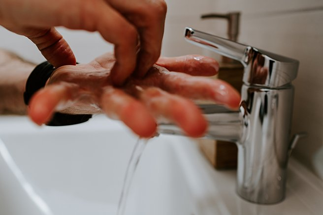 Close up on pair of hands being washed in sink