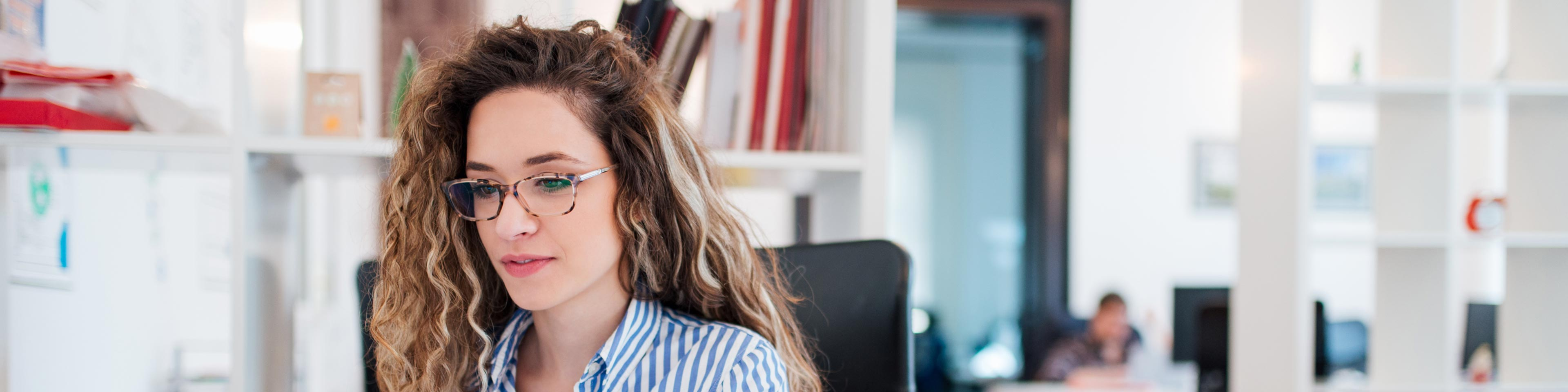 woman with curly hair reviewing employee benefits