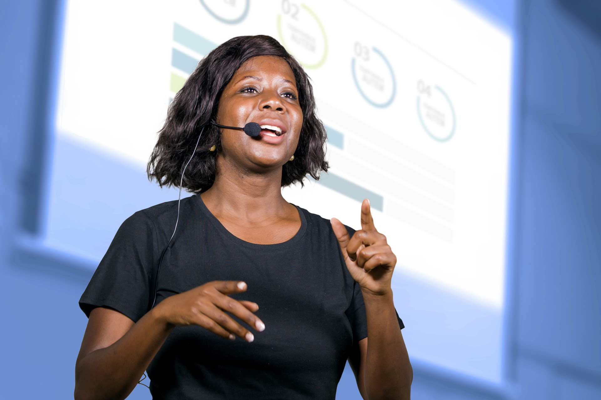 Woman presenting at conference with projector screen behind her