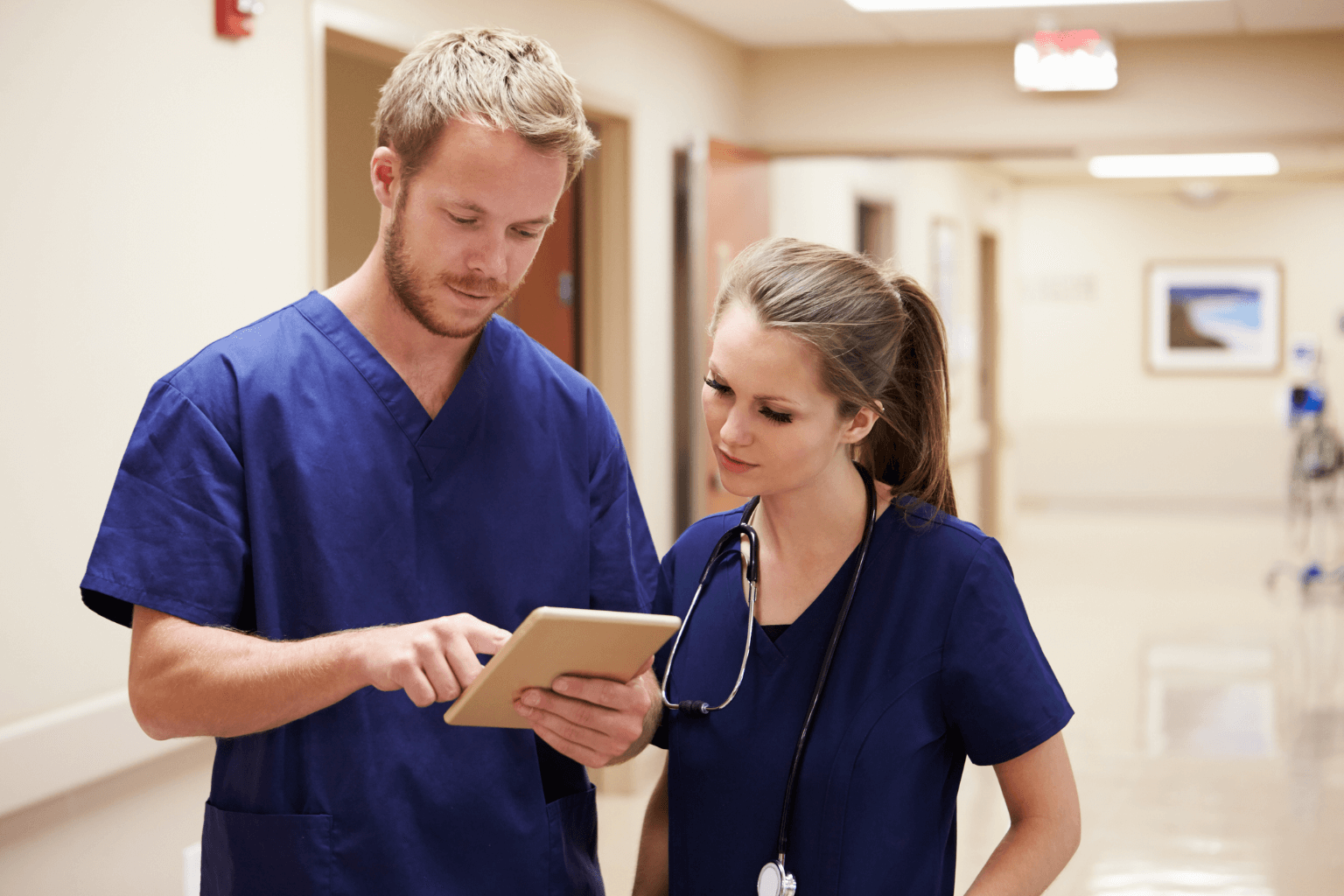 Medical-Staff-Looking-At-Digital-Tablet-In-Hospital-Corridorjpg