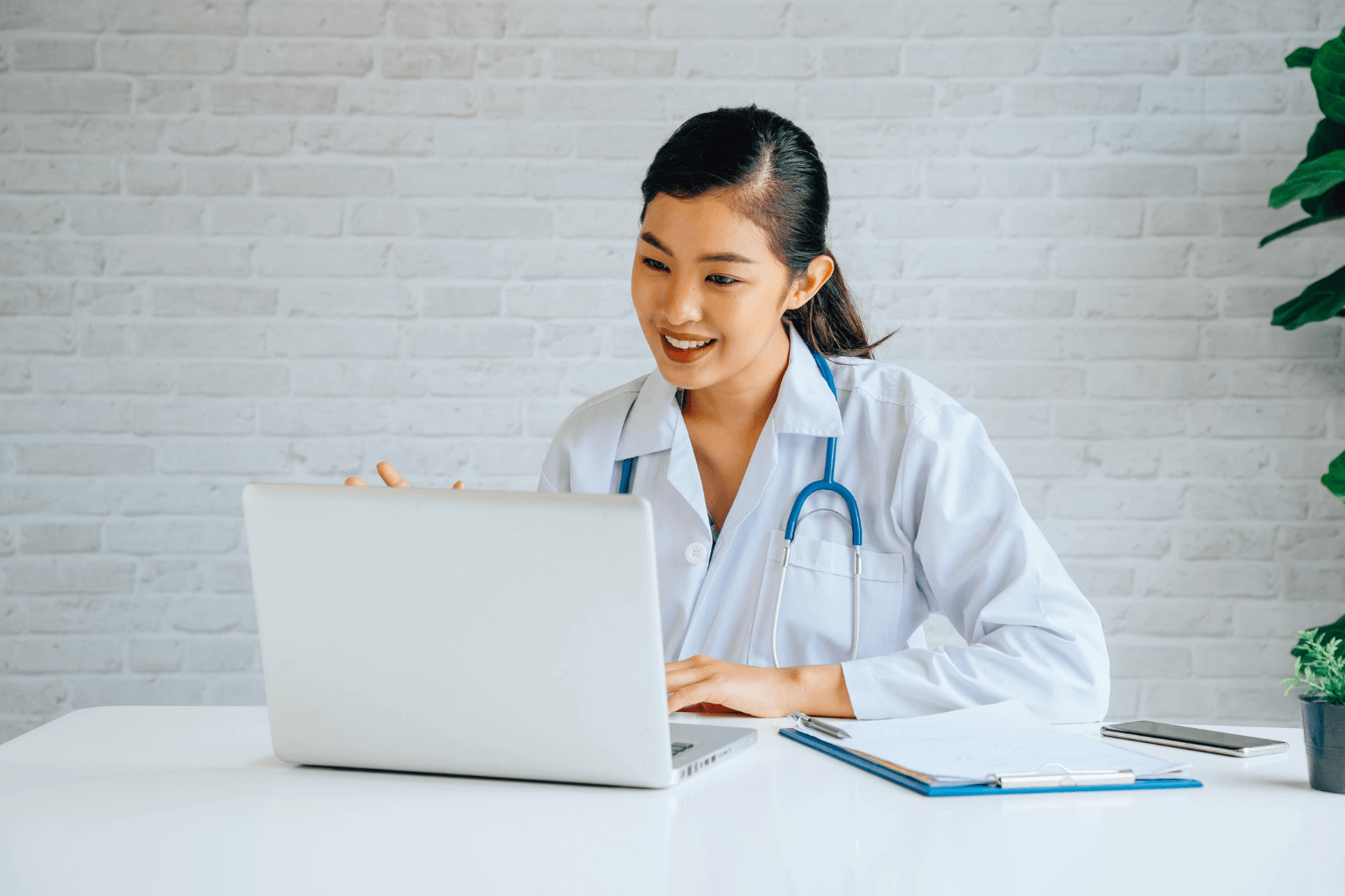 Asian female doctor working on a laptop