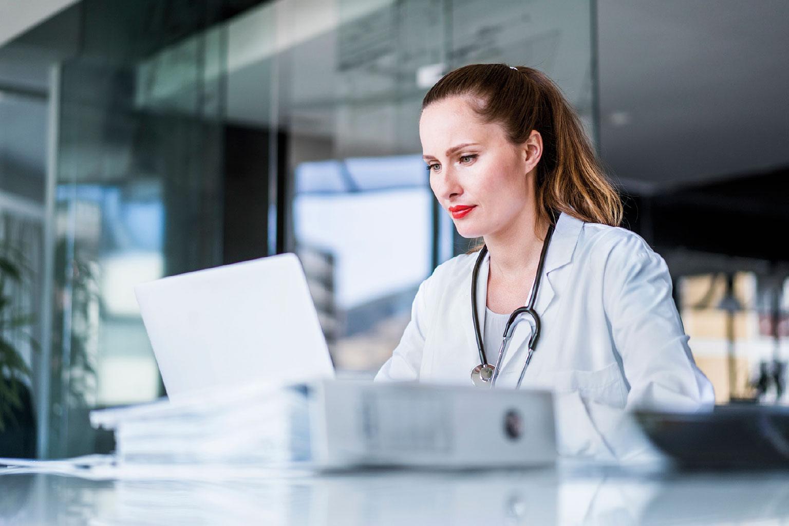Młoda lekarka przeglądająca dokumenty i pracująca z LEX