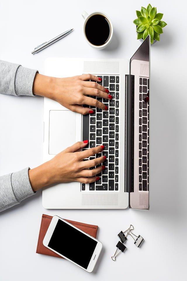 laptop met handen, telefoon en kopje koffie