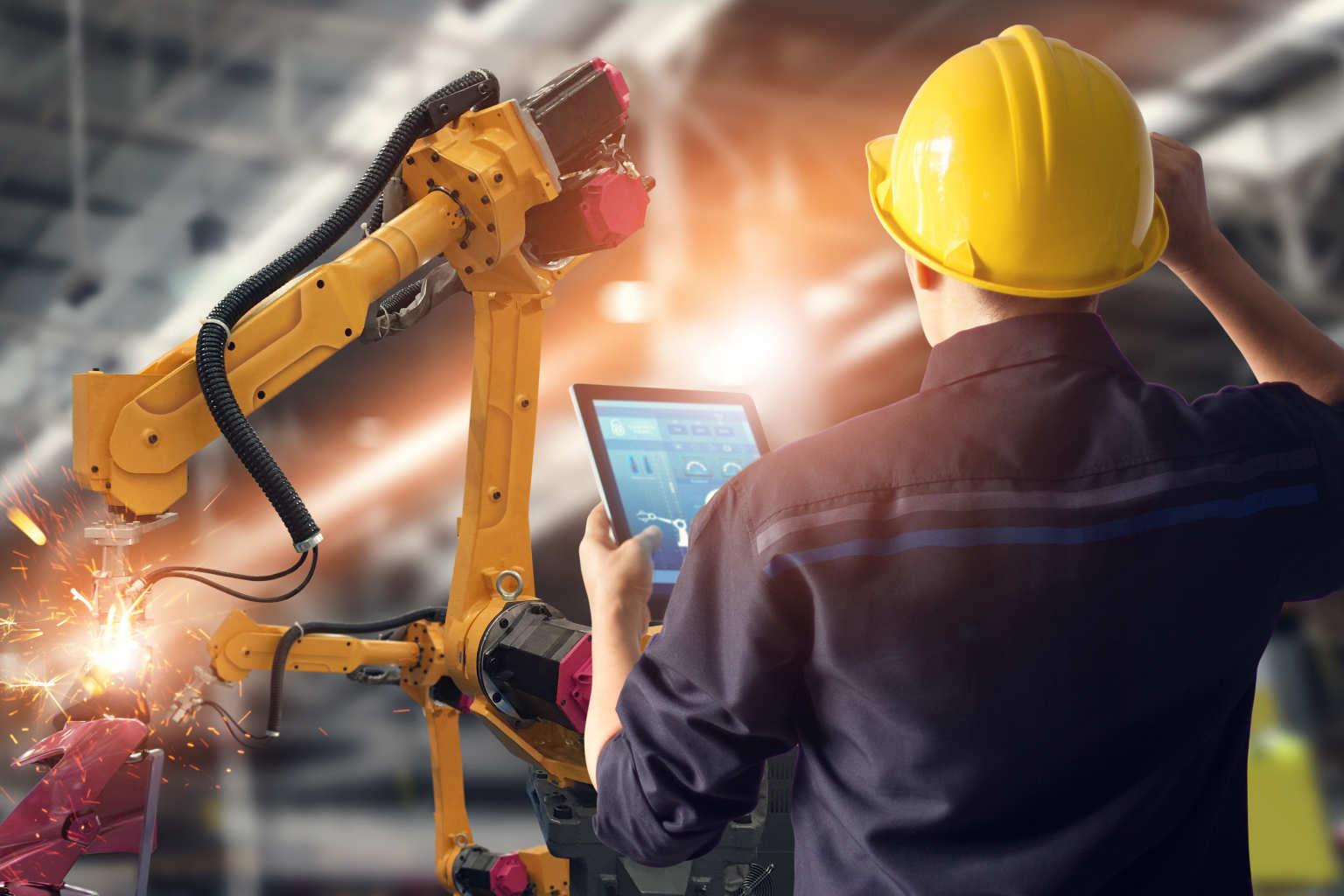 man holds tablet over robot