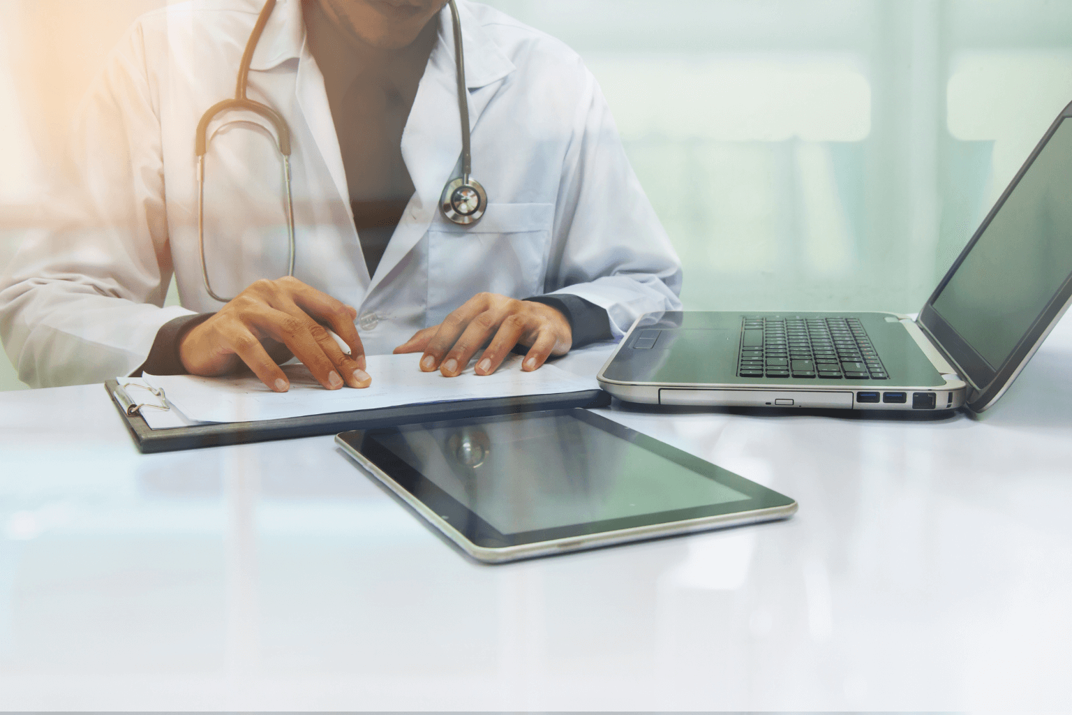 medicine-doctor-working-with-computer-notebook-and-digital-tablet-at-desk-in-the-hospitaljpg
