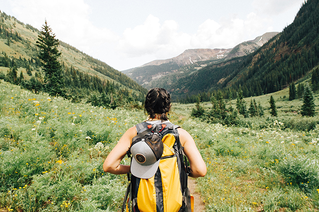 Woman with backpack hiking through mountainous area