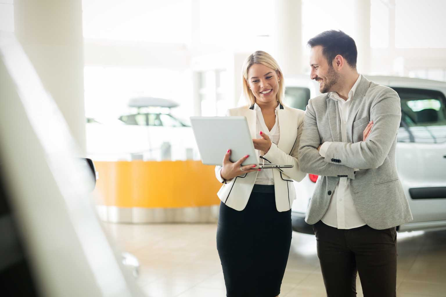 professional sales person selling a car in a car dealerships