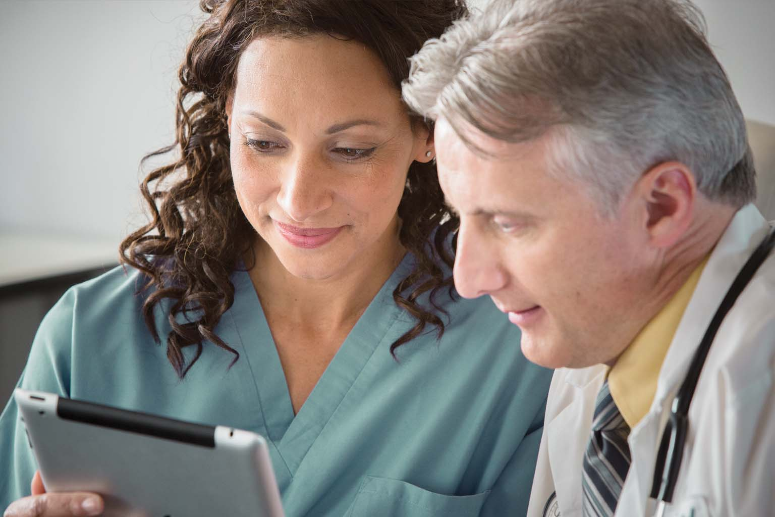 doctor and nurse looking at tablet