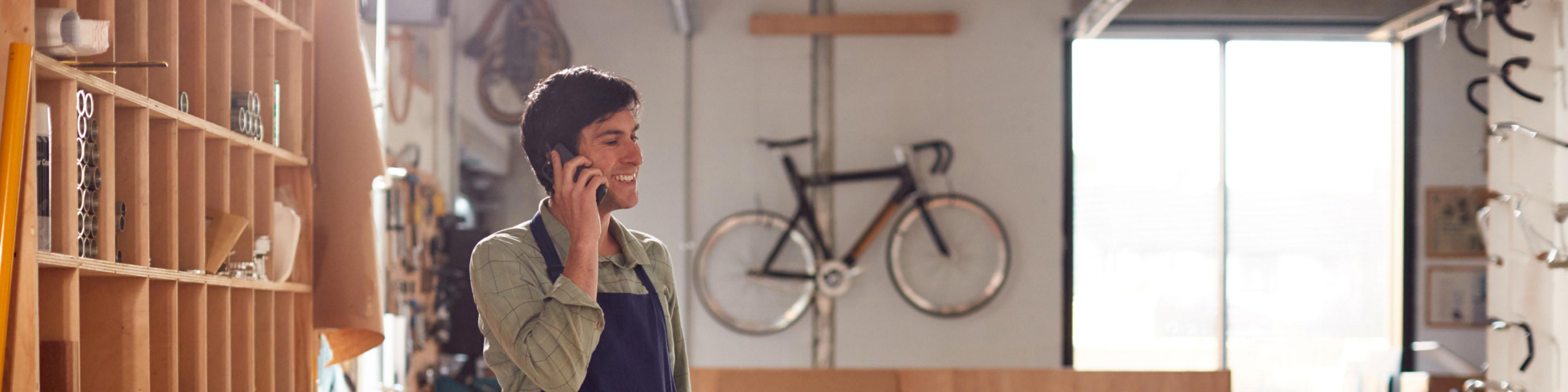 man in a bikeshop making a phone call about accounting for cash transactions