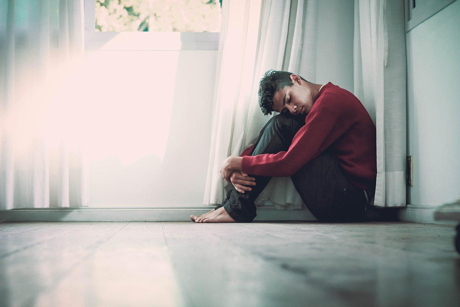 Young melancholy man sitting in corner, hugging his legs
