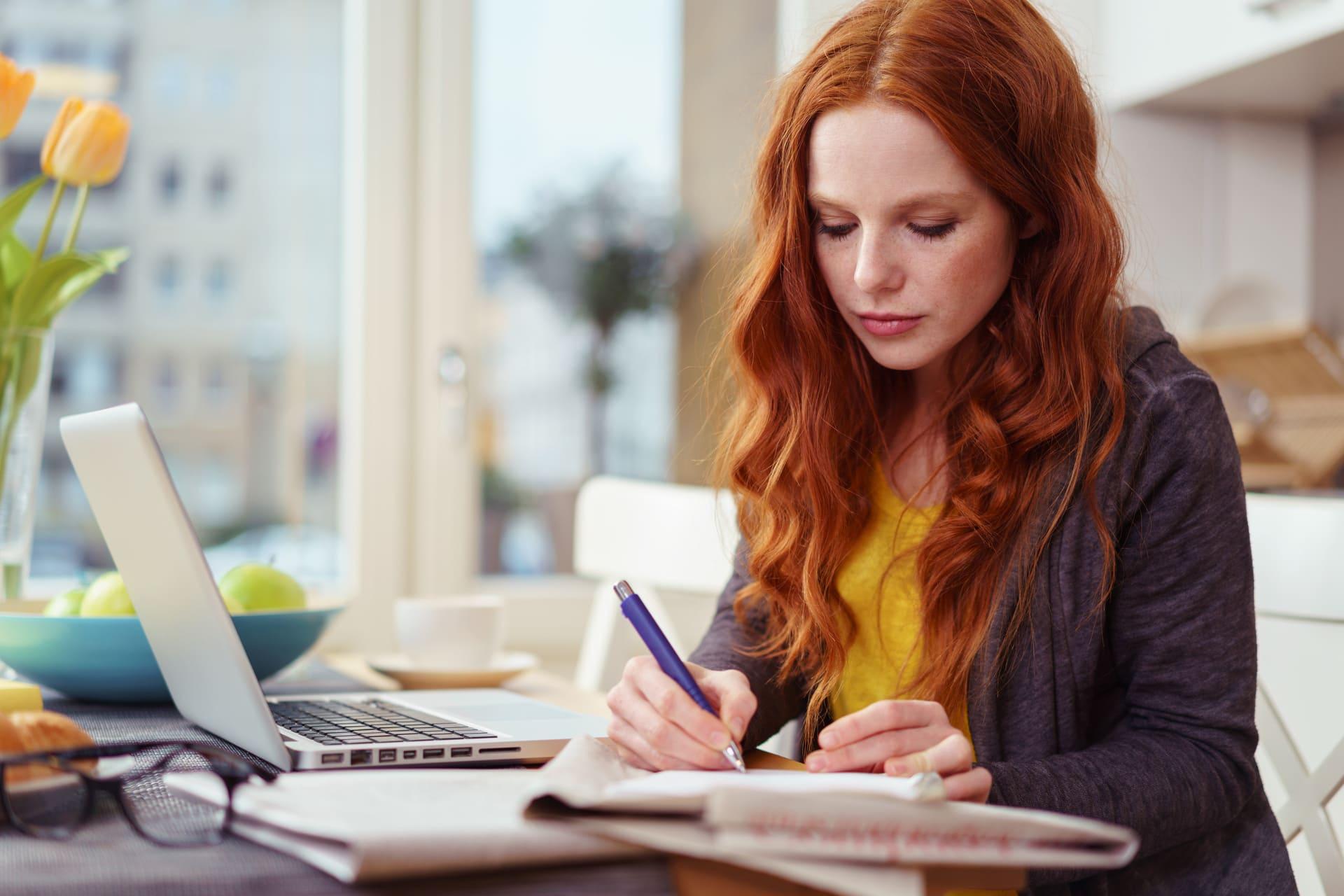 Vrouw aan het werk met laptop en notitieblok