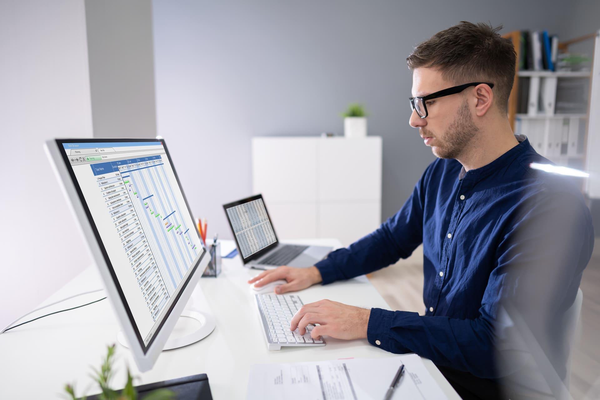 man bekijkt financiële rapportages via desktop computer