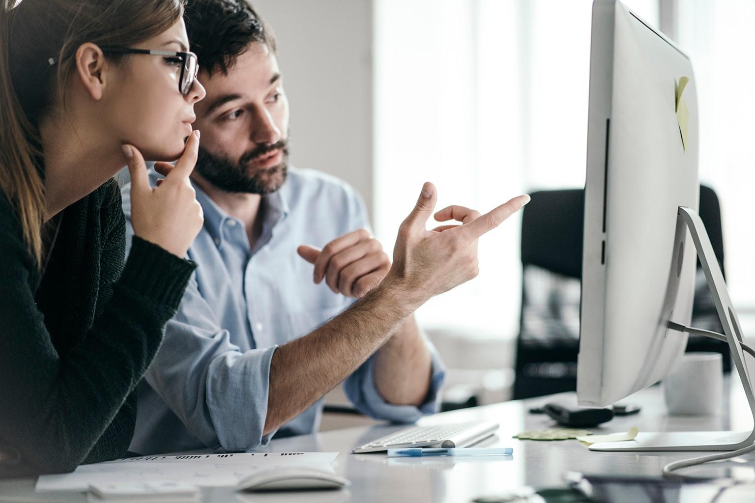 Kvinna och man framför en dator med bokslutsprogram från wolters kluwer