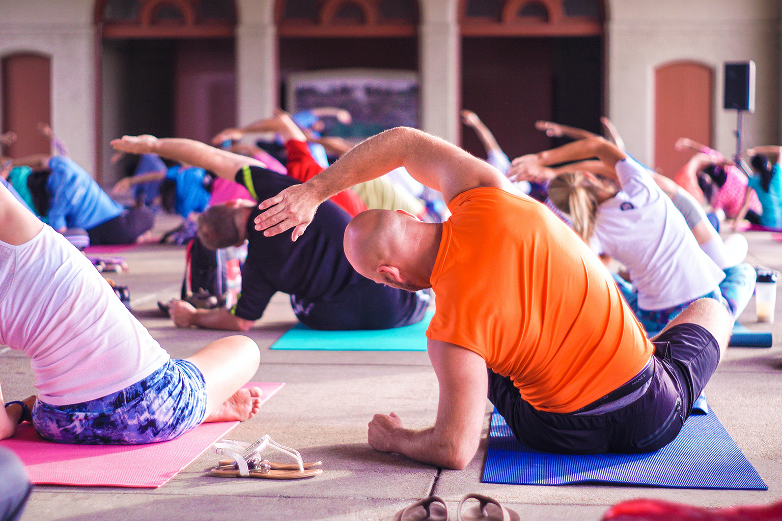 Yoga class sitting on their mats, stretching