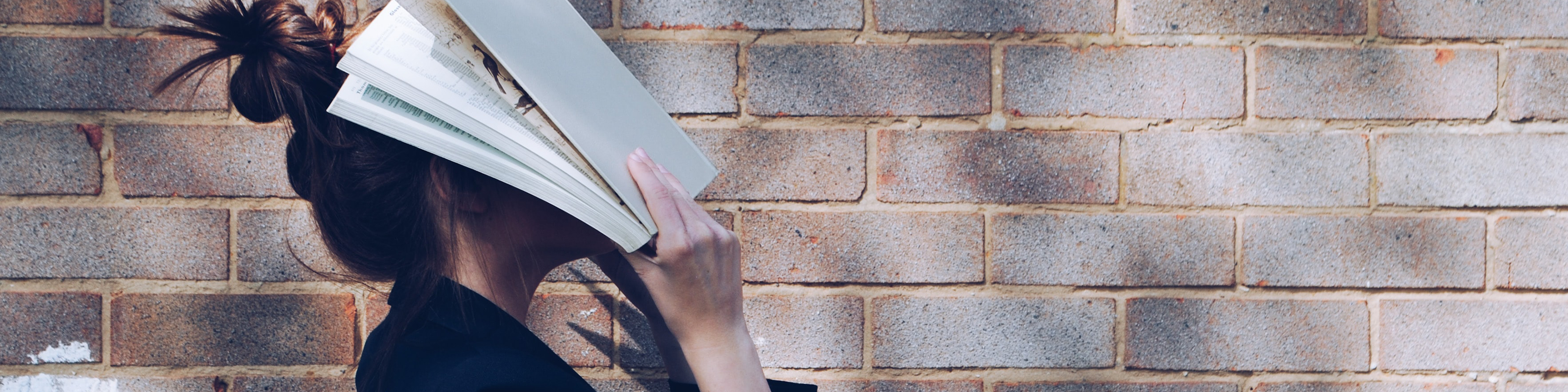 Woman standing outside next to brick wall, holding her open book up over her face