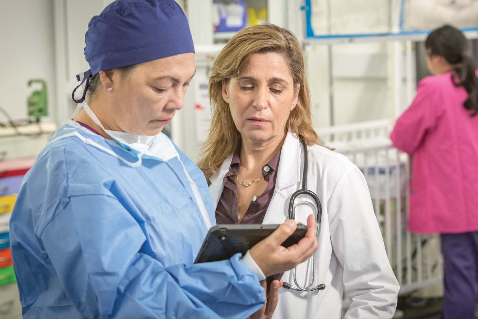 surgeon and doctory looking at tablet with nurse in background