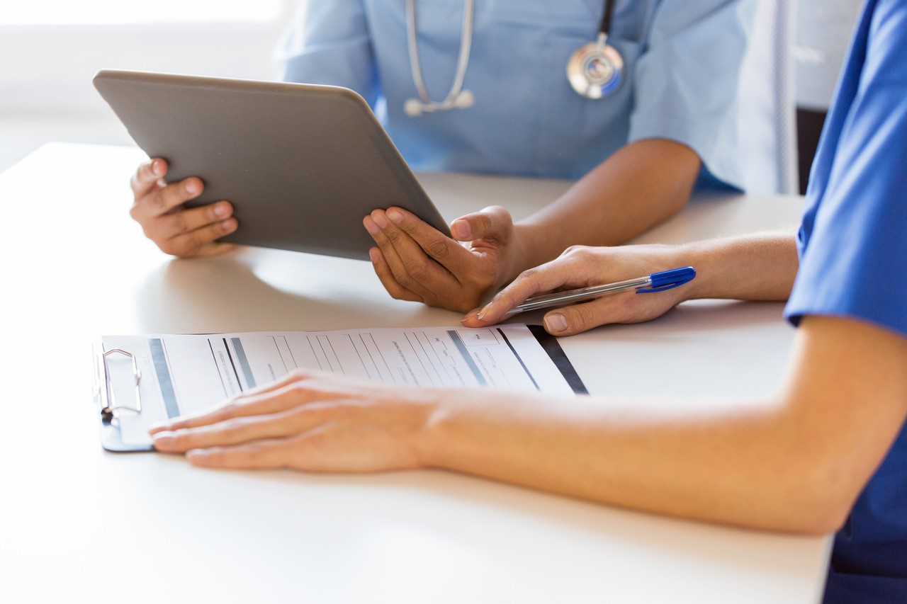 Two medical professionals looking at a tablet and a clipboard