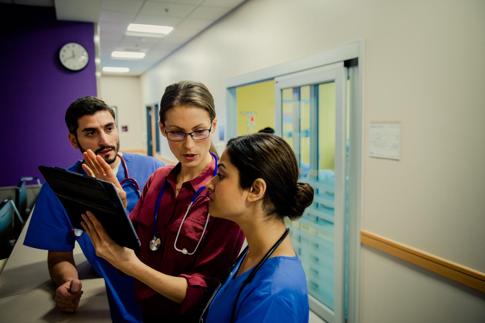 Three clinicians looking at computer