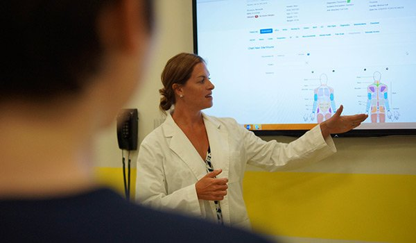 Instructor teaching nursing students with an educational EHR, DocuCare